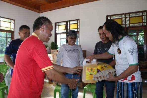 Pastor Bertje Karundeng Pr dari Patroki Lolak menerima sumbangan dari Paroki Kotamobagu untuk disalurkan kepada para korban banjir dan tanah longsor (PEN@ Katolik/ampcp)