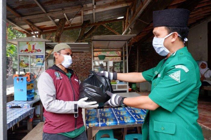 Ketua Pimpinan Wilayah GP Ansor Jawa Tengah Sholahuddin Aly menyerahkan paket sembako pada warga di Kecamatan Tembalang, Kota Semarang, (ANTARA/HO-Ansor Jateng)