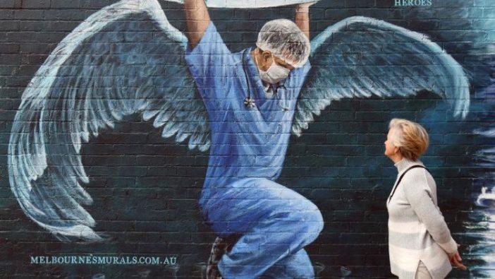 Seorang wanita melihat lukisan dinding seorang perawat yang bersayap sedang memegang bola dunia pada Hari Perawat Internasional, Australia (AFP)