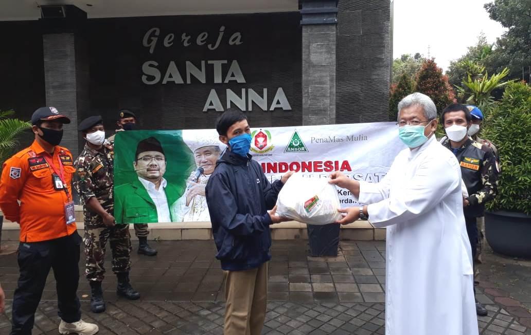 Pastor Albertus Sadhyoko Rahardjo SJ  menyerahkan bantuan sembako kepada yang membutuhkan