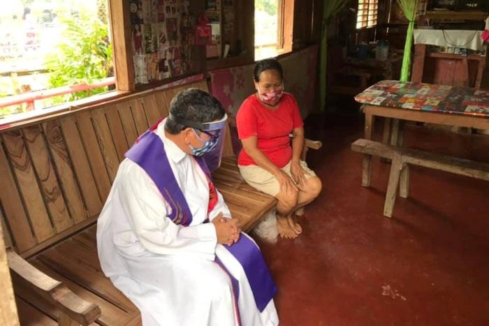 Pastor Amadeo Corpuz Alvero dari Paroki Santo Isidorus di Petani di McArthur, Leyte, mendengarkan pengakuan di dalam rumah penduduk desa, 22 April. FOTO PASTOR ALVERO