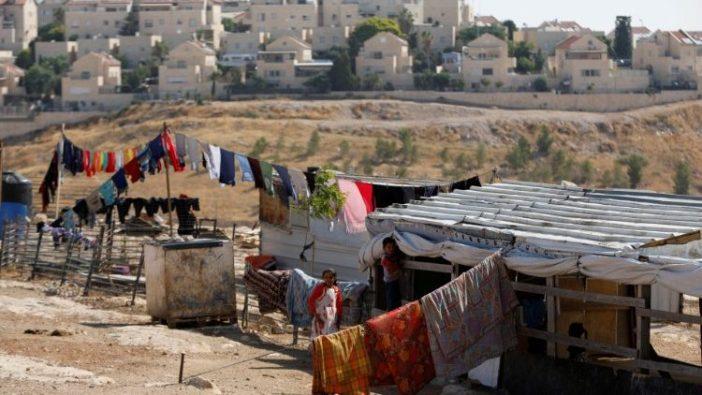 Keluarga-keluarga Palestina di kota Elzariya dengan latar belakang permukiman Yahudi Maale Adumin di Tepi Barat yang diduduki Israel.