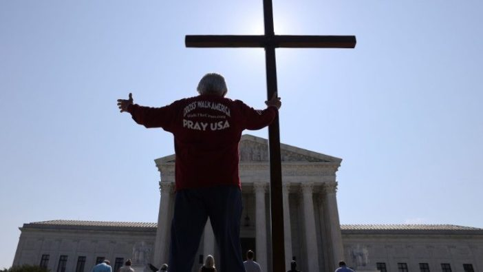 Seorang pria memegang salib di luar Mahkamah Agung AS