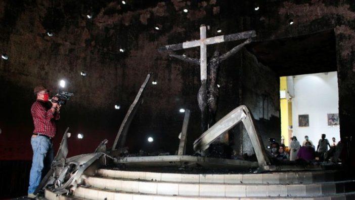 Umat Nikaragua berdoa di depan salib yang hangus terbakar di Katedral Managua
