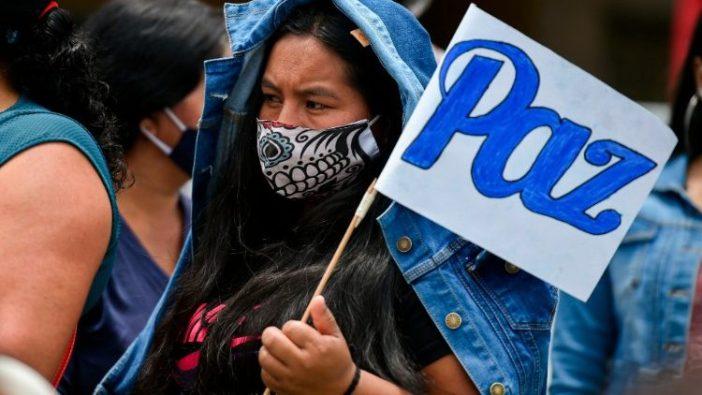 """Seorang wanita memegang bendera bertuliskan """"Damai"""" dalam pemakaman pria-pria yang dibunuh oleh kelompok bersenjata (AFP)"""