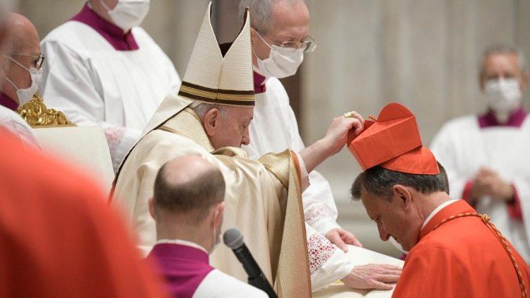 Paus memakaikan topi merah kepada kardinal yang baru diciptakannya dalam konsistori (Vatikan Media)