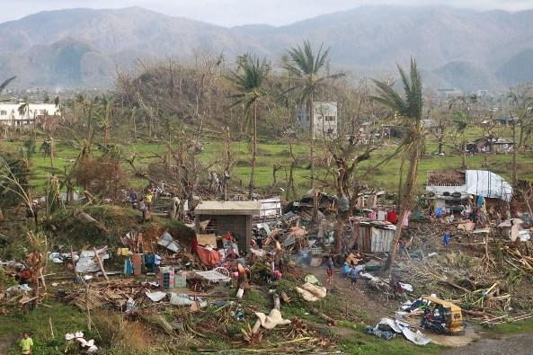 Orang-orang berdiri di luar rumah mereka yang hancur setelah Topan Super Rolly di Virac, Catanduanes, 2 November 2020. CIVIL DEFENCE PH PERTAHANAN PH