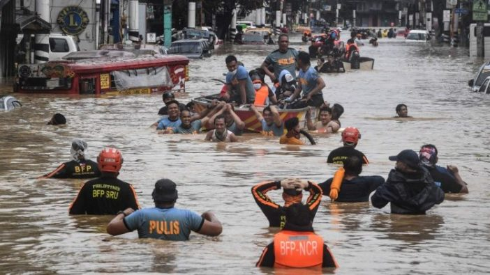Para penyelamat membantu warga di jalan yang banjir setelah Topan Vamco melanda Kota Marikina, Filipina (AFP)