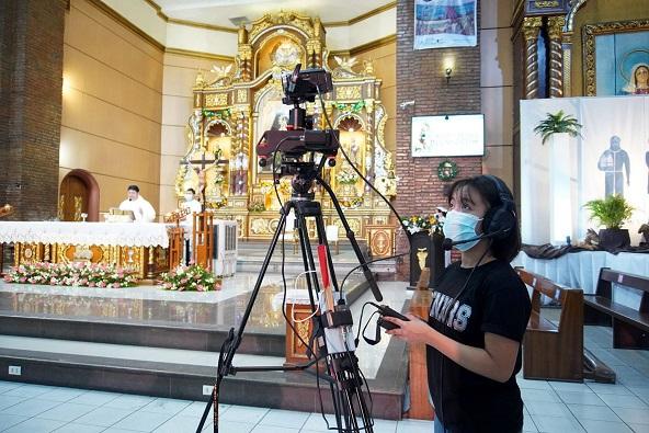 Seorang sukarelawan muda mengoperasikan salah satu kamera untuk Misa yang disiarkan langsung baru-baru ini di  San Mateo, Rizal.