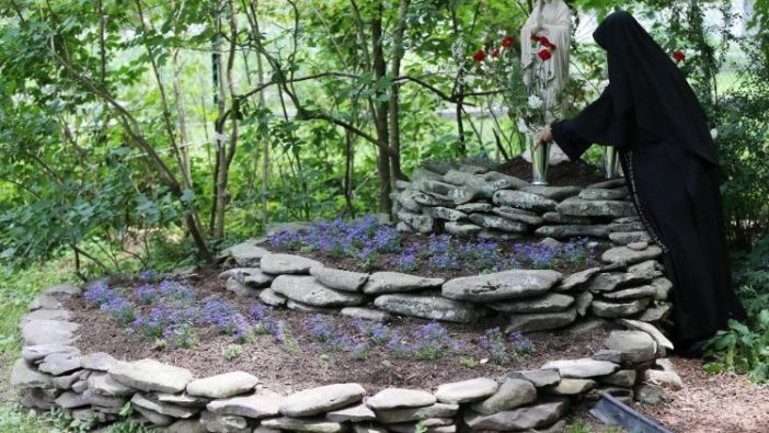 Seorang biarawati menghiasi patung Maria dengan bunga (ANSA)