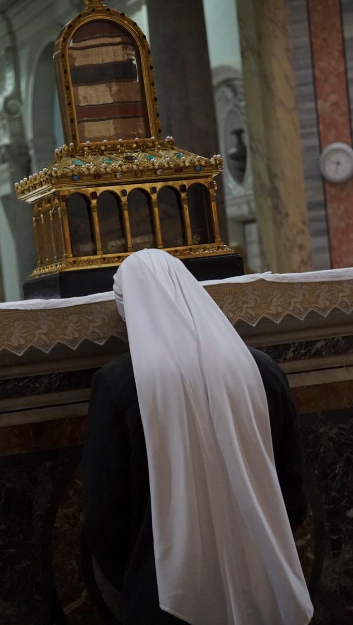 Seorang suster berdoa di depan relikui jubah Santo Yosef  © Serve del Signore e della Vergine di Matarà