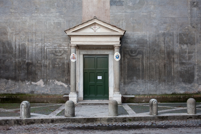 """Basilika Santo Nereus dan Santo Akhilleus. Di atas pintu masuk adalah """"titulus fasciolae"""" kuno. © gabriele gelsi   Shutterstock"""