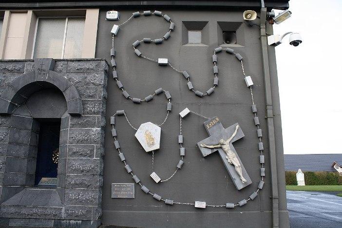 Rosario artistik Juga di belakang gereja adalah rosario indah dan sangat besar ini, dipasang di bagian depan untuk menyambut para peziarah. © Geyo John - CC BY-SA 3.0
