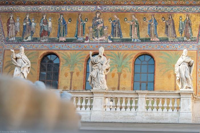 Basilika Santa Maria di Trastevere. Mosaik di bawah pedimen (bagian berbentuk segi tiga di bawah atap) yang menggambarkan Maria dan Anak Yesus yang diapit di kedua sisinya oleh lima wanita membawa lampu, mungkin mengacu pada gadis-gadis bodoh dan bijaksana dalam perumpamaan Injil. © Antoine Mekary | ALETEIA