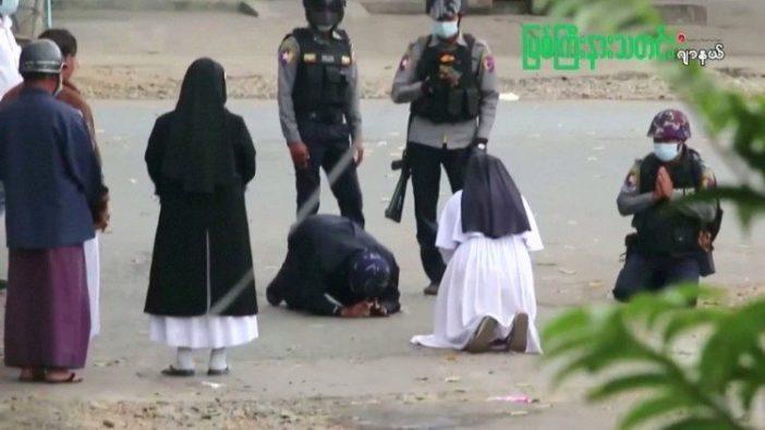 Suster Ann Rose Nu Tawng, biarawati Myanmar, berlutut di depan petugas polisi.