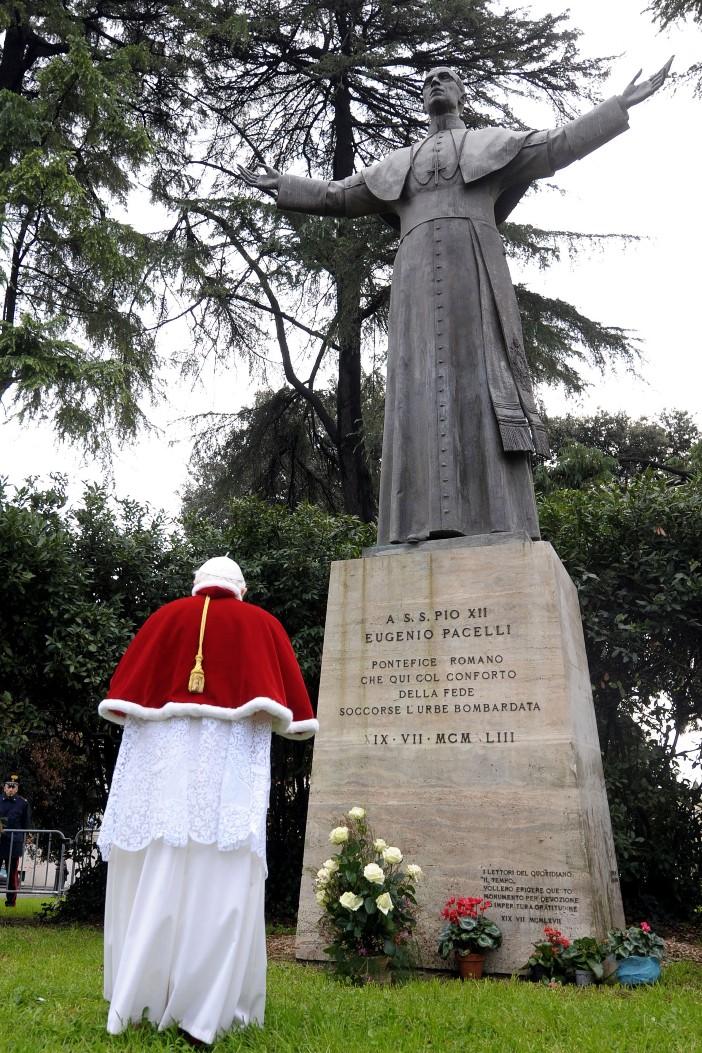 Basilika Santo Laurensius di Luar Tembok. Tahun 1964, patung Pius XII ditempatkan di lapangan di depan basilika. Patung itu dibayar dengan dana permohonan publik. Dalam foto itu, Paus Benediktus XVI berdoa di depan patung pendahulunya (2008). © Foto oleh OSSERVATORE ROMANO / AFP