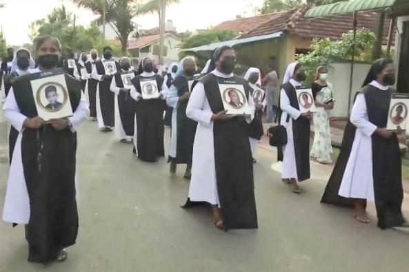 Para imam dan biarawati Katolik membawa foto-foto orang-orang yang meninggal dalam serangan Minggu Paskah 2019 dalam prosesi di dekat Gereja Santo Sebastianus di Katuwapitiya, Sri Lanka, 21 April 2021, ulang tahun kedua dari rangkaian ledakan yang menewaskan 269 orang. SCREENSHOT / VERBUM TV
