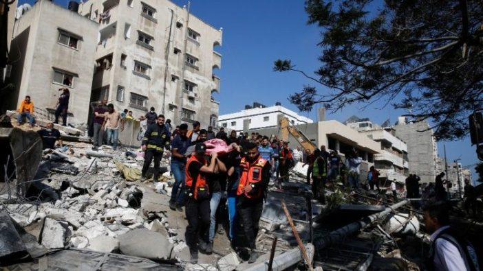 Petugas penyelamat membantu para korban di tengah puing-puing yang ditinggalkan oleh serangan udara Israel di Kota Gaza