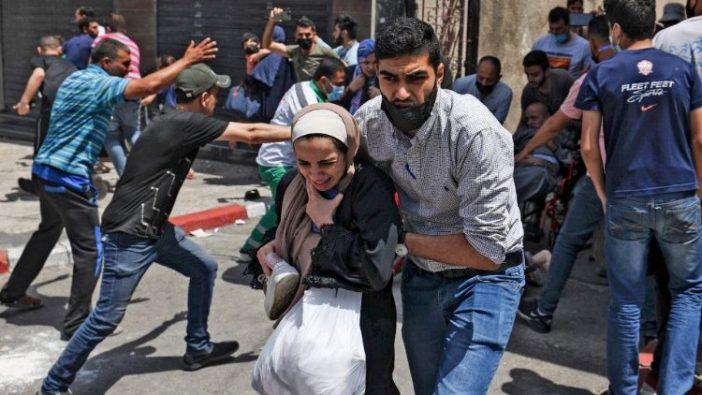 Warga Palestina mengevakuasi bangunan yang menjadi sasaran pemboman Israel di Kota Gaza, 11 Mei 2021 (AFP)