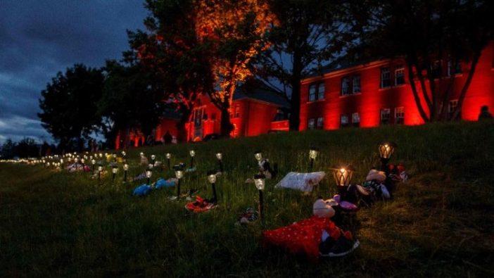 Sepatu, bunga, dan boneka di luar bekas Sekolah Asarama Indian Kamloops untuk menghormati 215 anak yang jenazahnya telah ditemukan (AFP)